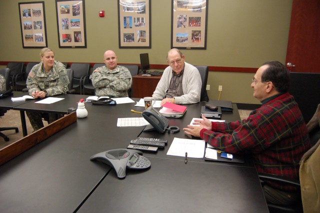 MILWAUKEE --- Retired Maj. Gen. Paul E. Lima (right), Milwaukee Recruiting Battalion Community Advisory Board chair; and John Curtis, vice chair, review the status of Milwaukee Company's community advisory board with Capt. Carissa Schessow, commander, and 1st Sgt. Gregory Cowper, in December 2010.