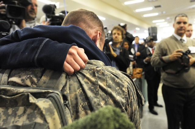 """A Soldier comes home to begin his two week """"rest and recuperation"""" (R&R) time and is embraced by a loved one at Dallas/Fort Worth International Airport  on Jan. 11, 2011. The U.S. Military R&R program today observed the one-millionth soldier transported home from Iraq and Afghanistan."""