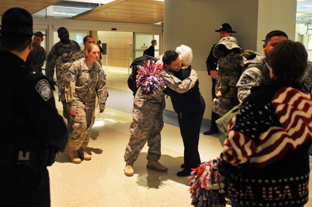 """Welcome Home A HeroAca,!A!"" Volunteers greet Soldiers at  Dallas/Fort Worth International Airport on Jan. 11, 2011.  The Soldiers were returning from their deployment to begin their two week ""rest and recuperation"" time."
