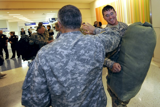 """Chief of Staff of the US Army, Gen. George W. Casey Jr.,  greets a Soldier at Dallas/Fort Worth International Airport who's returning from his deployment to begin his two week """"rest and recuperation"""" (R&R) time on Jan. 11, 2011. The U.S. Military R&R program today observed the one-millionth soldier transported home from Iraq and Afghanistan."""