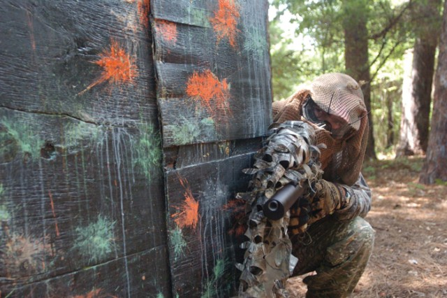 Larry Wiegart peeks around the corner of a paint-covered barrier at Woodland Paintball Area.