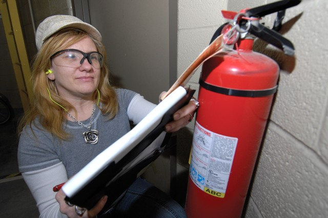 Rose Brown, painter, checks the tags on a fire extinguisher in the Component Paint Branch.