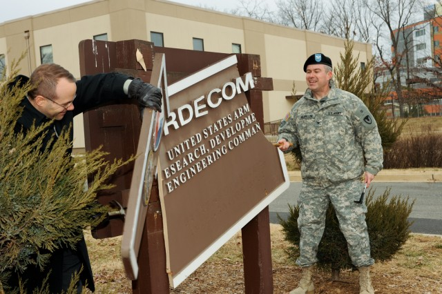 Mike Olin of Communications-Electronics Research, Development and Engineering Center and RDECOM Chief of Staff Col. John Kilgallon remove the command sign Jan. 7 at Fort Belvoir, Va. Seven military and civilian employees helped with a large socket wrench, hammer, mallet and pry bar.