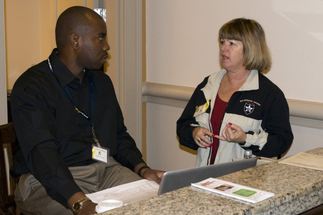 Capt. Fredrick Waters and Bonnie McCarthy, both support staff from the 200th Military Police Command, discuss a transportation issue during a recent Yellow Ribbon Reintegration Program workshop in Orlando, Fla.