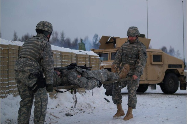 Soldiers of the 709th Military Police Battalion replicate evacuating a casualty as part of a training scenario during a combat outpost live-fire training exercise on Range 201 on the Grafenwoehr Training Area.  The range differs from other ranges because it provides units a 360 degree fires capability.