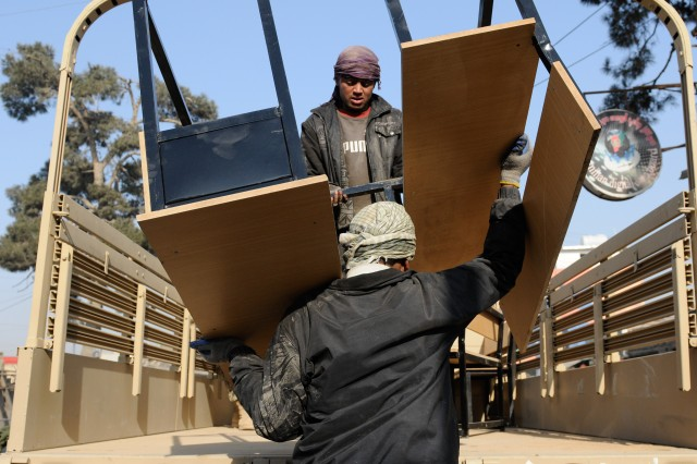 Local workers load one of the 75 desks built for the Khasapaz Primary School here in a joint effort between the Command Emergency Response Team of the 87th Combat Sustainment Support Battalion, 101st Sustainment Brigade and the 5th Kandak, 3rd Brigade, 209th Afghan National Army Corps.(U.S. Army photo by Pfc. Michael Vanpool, 101st Sustainment Brigade)