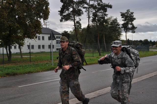 Staff Sgt. Edson Rodriguez, an 18th Engineer Brigade intelligence analyst, runs beside a Soldier from 464th Special Engineer Battalion during a ruck march in Speyer, Germany, Oct. 20. Soldiers participating in the event were doing so to earn the German Armed Forces Badge for Military Proficiency.