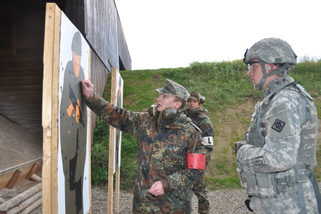 Pfc. Kevin Marberry, an 18th Engineer Brigade vehicle driver, reviews his target with Soldiers from the 464th Special Engineer Battalion, after firing the P8 9mm pistol. Soldiers qualified on the G36 5.56mm machine gun and P8 9mm pistol in order to earn the Schutzenschnur, or German Marksmanship Badge.