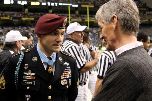 Medal of Honor recipient Staff Sgt. Salvatore Giunta and Secretary of the Army John McHugh converse at the 2011 All-American Bowl.