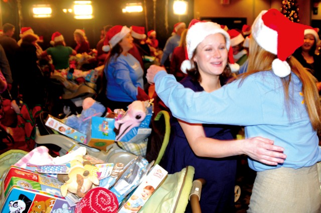 """Jennifer Overmyer, left, wife of Capt. Thomas Overmyer, 1st Battalion, 32nd Infantry Regiment, receives a gift cart from a Walmart employee Dec. 23, during Operation Shower. More than 100 pregnant spouses received strollers, diapers and other necessities for newborn babies during a live taping of the """"Today"""" show held at the Commons."""