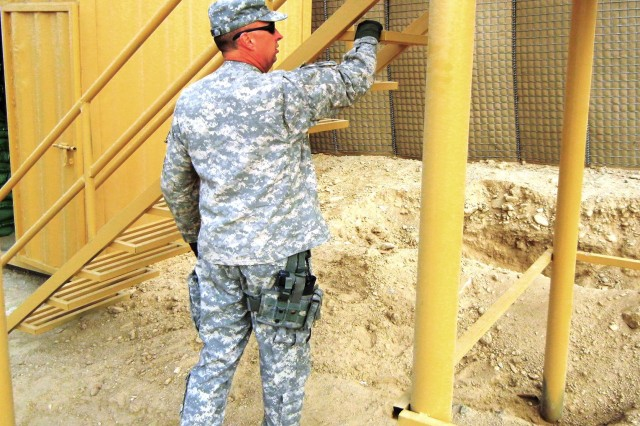 Command Sgt. Maj. David J. Vincent inspects the welding on stairs at a guard tower at the Deh Sabz Forward Operating Base near Kabul.