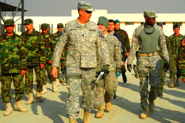 Command Sgt. Maj. David J. Vincent, DCOM-Regional Support, followed by Capt. Karl Heineman and Master Sgt. Arthur Tinsley, RSC-Capital Logistics NCOIC (right), review Afghan soldiers conducting drill and ceremony at Ghazi Military Training Center near Kabul.