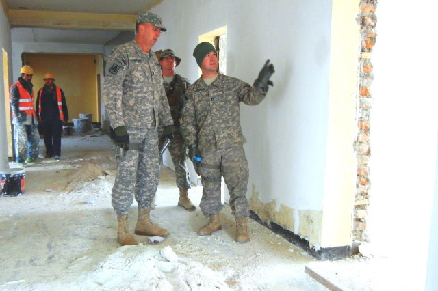 Command Sgt. Maj. David J. Vincent, DCOM-Regional Support, and Capt. Karl Heineman, a lead engineer for RSC-Capital, check a door frame in an Afghan Army barracks under renovation at the Ghazi Military Training Center near Kabul. The center is run by the Turkish military and is designed for noncommissioned officer training.