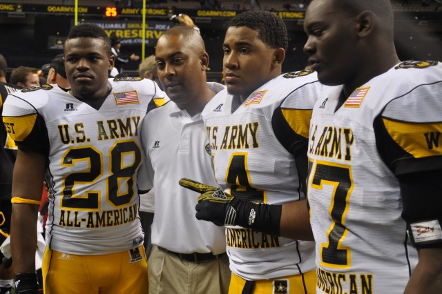 U.S. Army All-Americans Malcom Brown, Ryan Simmons and Marquis Anderson of Steele High School in Cibolo pose with their head coach, Mike Jinks, who was an assistant coach for the West squad.
