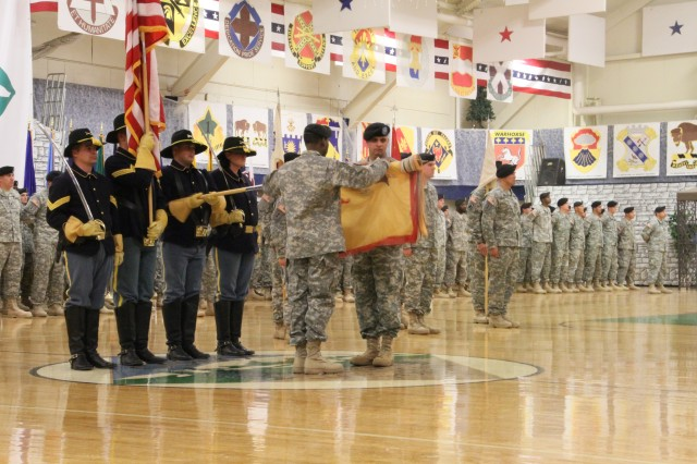 Col. Thomas A. Rivard and Command Sgt. Maj. Colvin Bennett uncase and unfurl the 68th Combat Sustainment Support Brigade guidon during the change of command and transfer of authority ceremonies Jan. 6 at the Special Events Center.