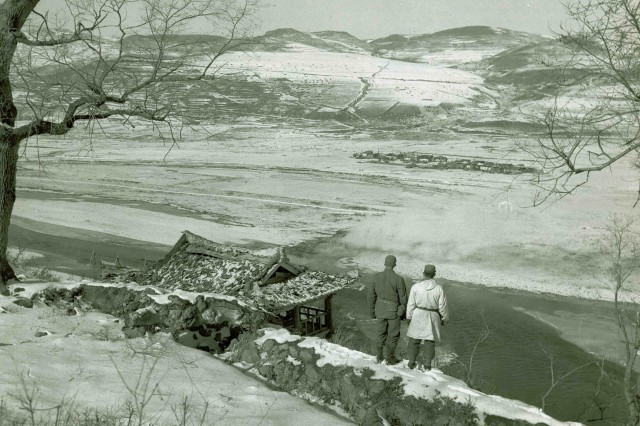 "Two American Soldiers gaze across the Yalu River to the mountains of Manchuria on November 21, 1950. This photograph was featured in Karl Warner's November 14, 2010, ""This Week in Army History,"" article ""Combating Cold Korea,"""