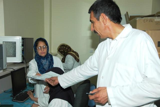 Col. Sayed Azim, Herat Regional Medical Hospital, Afghanistan, commander, examines inpatient medical records.