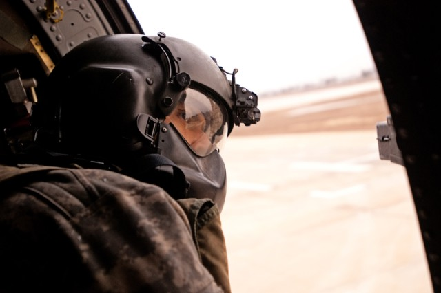 Black Hawk crew chief Spc. Titus Richardson leans out of his crew window during a mission near Baghdad, Jan. 10. Assigned to A Company, 2nd General Support Aviation Battalion, 1st Aviation Regiment, Enhanced Combat Aviation Brigade, 1st Infantry Division, Richardson and other Black Hawk crews transport military and civilian VIPs between U.S. bases around Iraq.