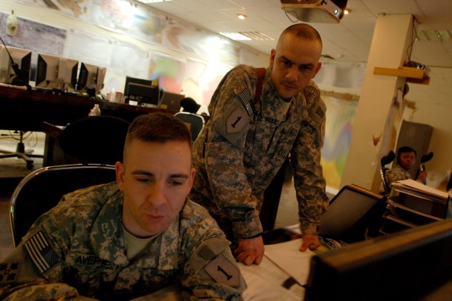 Sgt. Kevin Averre (left) and Chief Warrant Officer 2 Anthony Campbell look at a computer in the tactical operations center of the Enhanced Combat Aviation Brigade, 1st Infantry Division. The operations center tracks aviation operations across the country, as well as maintains situational awareness for the brigade's commander. Averre and Campbell are assigned to the brigade's headquarters company. (Photo by Spc. Roland Hale)