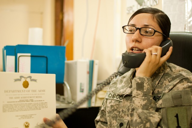 Spc. Anita Chacon, a human resource specialist deployed to Iraq with the Enhanced Combat Aviation Brigade, 1st Infantry Division, speaks with a customer from her office on Camp Taji, Jan. 14. Chacon, a native of Fontana, Calif., has helped her section process more than 3,000 awards since last March. (Photo by Spc. Roland Hale)