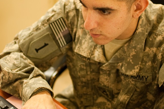 Pfc. Joey Lamura, a human resources specialist deployed to Iraq with the Enhanced Combat Aviation Brigade, 1st Infantry Division, works in his office on Camp Taji, Jan. 14. Lamura, a native of Tampa, Fla., keeps track of his brigade's man-power at locations across Iraq. (Photo by Spc. Roland Hale)
