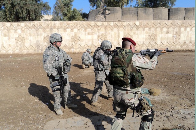 1st Lt. William Simpson (second from right), with Battery A, 1st Battalion, 7th Field Artillery Regiment, 2nd Advise and Assist Brigade, 1st Infantry Division, United States Division-Center, native, and Iraqi Army 2nd Lt. Mustafa Mohammed Khazal (right) compete in a platoon leader shootout Jan. 3 as Sgt. Benjamin Rodgers (left) acts as range safety officer.