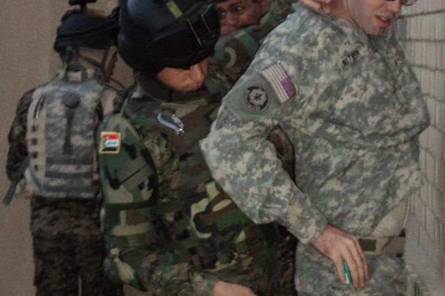 Spc. Zaine Mather (right), with Battery A, 1st Battalion, 7th Field Artillery Regiment, 2nd Advise and Assist Brigade, 1st Infantry Division, United States Division-Center, is searched by an Iraqi Army Soldier during a training exercise at Joint Security Station Old MoD, Iraq.