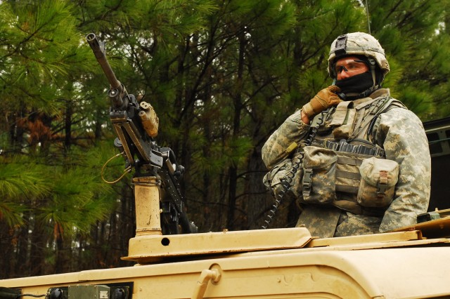 FORT HOOD, Texas- Spc. Jon King, a Longmont, Colo. native and a mortarman with 1st Battalion, 8th Cavalry Regiment, 2nd Brigade Combat Team, 1st Cavalry Division, listens for instructions over a radio as his unit prepares to embark on a patrol during an exercise at the Joint Readiness Training Center on Fort Polk, La., Jan. 11.