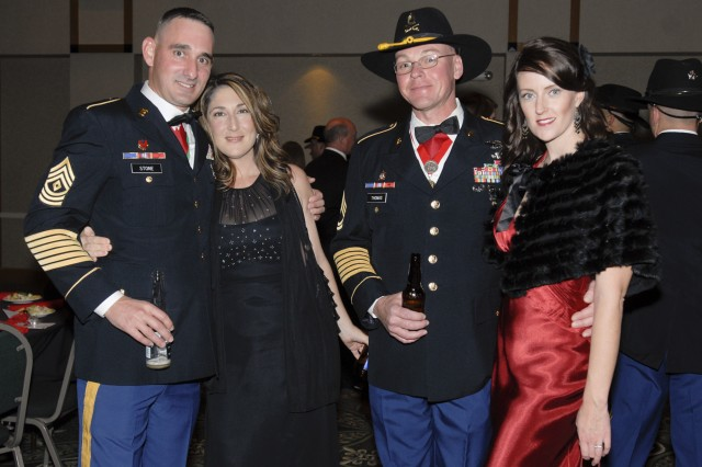 FORT HOOD, Texas - 1st Sgt. Kenneth Stone, his wife Julia (left), Sgt. 1st Class Ted Thomas and his wife Rebecca pose for a photo at the Greywolf Gala, Jan. 7 at the Killeen Civic Center.