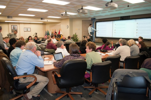 Panelists gather Wednesday for the Facebook Town Hall. Each official was partnered with a public affairs officer and a computer. Information technology experts were on hand to handle any computer problems. The Facebook page was displayed on three large screens for everyone to view incoming questions. An after action review is scheduled for this week to discuss what went well and what can be improved.