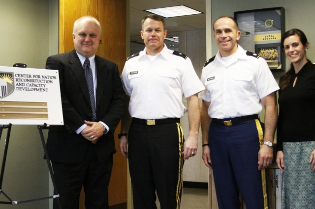 John Farr (left), Center for Nation Reconstruction and Capacity Development director; Brig. Gen. Timothy Trainor, Dean of the Academic Board; Lt. Col. Kenneth McDonald, CNRCD associate director; and Jamie Enos, Systems Engineering strategic communications specialist, are some of the main players who brought  CNRCD to fruition at West Point. The official unveiling of the new Center for Nation Reconstruction and Capacity Development on Jan. 11 came with a message to the department heads in attendance. Three months since it was approved as a center of excellence at West Point, the CNRCD is operational and will be ripe with opportunities for cadets and faculty academy-wide. Photo by Mike Strasser, West Point Public Affairs