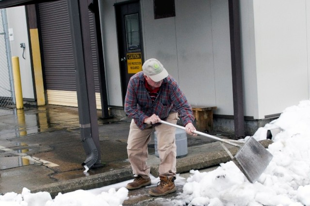Geno Buchanan clears snow from the entrance to a shop in Anniston Army Depot's Nichols Industrial Complex Jan. 11.