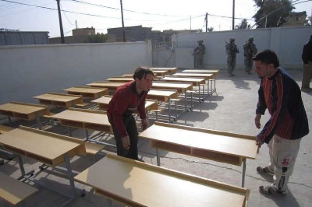 Desks for the Athathib School are unloaded Jan. 5. Soldiers with the 3rd Battalion, 7th Infantry Regiment, 4th Advise and Assist Brigade, 3rd Infantry Division, provided the desks through the Commander's Small Scale Projects fund, a sublet of CERP.
