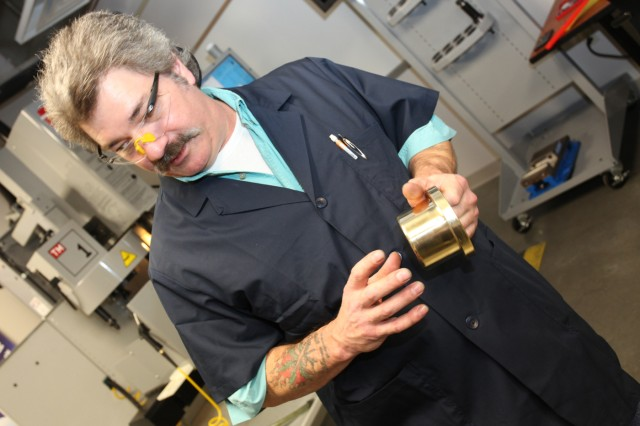 Computer Numeric Controlled Instructor, Bruce Walker, explains the process used to fabricated replacement parts for The Old Guard's Caisson Wagons. Walker and other staff of the Ordnance School's Metalworking Services Training Division here are currently using industry leading technology to replicate ceremonial inserts for the horse breast collar plate, brass wagon wheel spindle caps and wheel locks for The Old Guard.