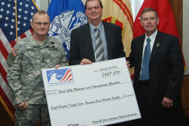 Maj. Gen. Yves J. Fontaine, Army Sustainment Command commander and Illowa Bi-State Combined Federal Campaign honorary chair, presents Rick Widdell, principal combined fund organization representative, with a check for $827,470 to charities designated by federal and postal employees as Joel Himsl, garrison manager, U.S. Army Garrison-Rock Island Arsenal looks on.