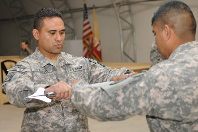 Maj. Robert Le'iato, 4th Financial Management Company commander (left), assists 1st Sgt. Francisco Acosta, 4th FM Co. first sergeant, uncase the unit guidon during a transfer of authority ceremony at Kandahar Airfield, Afghanistan, Jan. 17. (U.S. Army photo by Spc. Jennifer Spradlin, 16th Mobile Public Affairs Detachment)