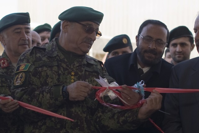 Gen. Sher Mohammad Karimi, Afghan National Army chief of general staff, helps Brig. Gen. Habibullah, who only goes by one name, chief of Construction Management Property Division, cut the second ribbon at the Afghan National Security Force Facility Engineer Technical Training School during the school's ribbon-cutting ceremony in Kabul, Afghanistan, Jan. 23, 2011. The schoolhouse trains students from the Afghan National Army and Afghan National Police in electrical work, carpentry, plumbing, masonry, heating venting and cooling, painting and metallurgy. The skills learned by these students will be used to maintain bases throughout Afghanistan.
