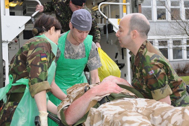 British and American medical Soldiers work together to unload a simulated casualty from an ambulance before entering the hospital during Operation Starlight II in Strensall, England, Jan. 21.
