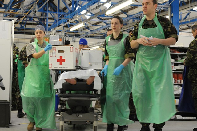 Sgt. Zoreida Galindo, a medic with the 67th FST (ABN), works with British medical Soldiers to quickly move a simulated patient into the operating room during Operation Starlight II in Strensall, England, Jan. 23.