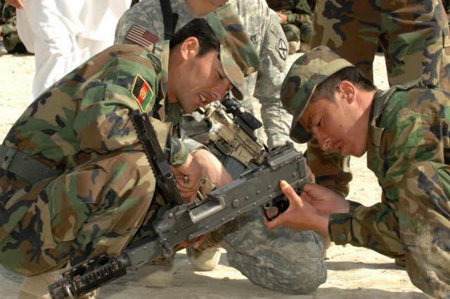 Two Afghan National Army recruits adjust a weapon during a weapons qualifying course at Kabul Military Training Center. Recruits take part in a 6-week basic military training program when they enlist in the ANA.
