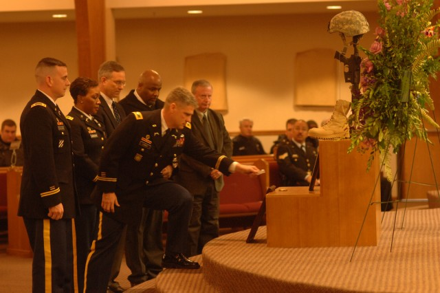Col. Steven Lynch, Joint Force Headquarters, National Capital Region and provost marshal Military District Washington places his commander's coin at the Fallen Soldier display for Sgt. Zainah Creamer, 212th Militray Police Detachment, during a memorial ceremony Friday at Fort Belvoir's Woodlawn Chapel. Creamer was killed in Afghanistan by an I.E.D., Jan. 12 while on routine building search with her working dog Jofa. Creamer 28, was on her third deploment, the previous two were to Iraq. Jofa was unhurt in the blast and will be returned to the MP unit.