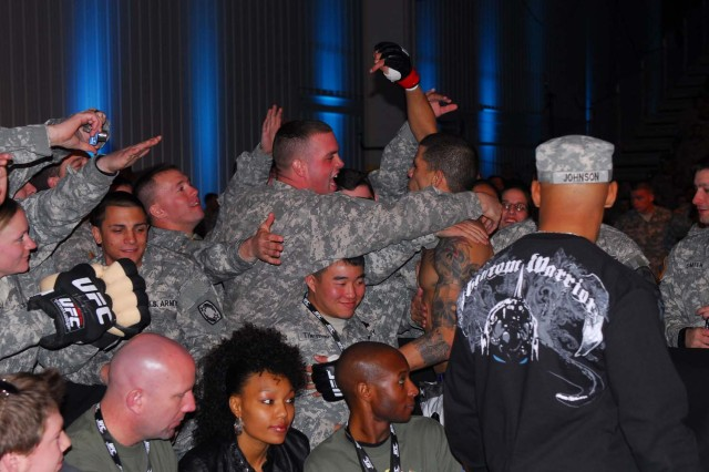 Following his win in the Welterweight bout, DaMarques Johnson greets several overjoyed fans while his team hands out hats and T-shirts supporting Johnson during the UFC Fight for the Troops Jan. 22, 2011, at West Fort Hood, Texas. Fight for the Troops is raising awareness for UFC Intrepid Fallen Heroes Fund, which is a leading effort in supporting servicemembers who suffer from Traumatic Brain Injuries sustained from overseas tours.