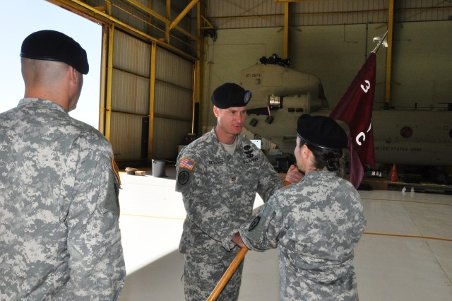 "Major Jacob Dlugosz (center), outgoing commander, C Company, 3rd Battalion, 25th General Support Aviation Battalion (GSAB), 25th Combat Aviation Brigade, passes the company guidon to Lt. Col. Lori Robinson, commander, 3-25th GSAB, during his change of command ceremony on Wheeler Army Airfield, Jan. 19. Dlugosz relinquished command of the ""Dustoff"" MEDEVAC company to Maj. Jeremiah Simpson.  (Photo by: Sgt. 1st Class Tyrone C. Marshall Jr.  25th Combat Aviation Brigade Public Affairs)"