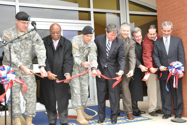 The U.S. Army Materiel Command's Band cut the ribbon on its new facility here, Monday. From left to right: Lt. Gen. James H. Pillsbury, deputy commanding general of AMC; Curtis L. Clark, Deputy to the Garrison Commander; Chief Warrant Officer Peter C. Gillies, the AMC Band Commander; Joe Ritch, chairman of the Tennessee BRAC Committee; Thomas J. Vajentic, chief of the AMC Transformation Team; unknown; Mike Edwards, lead engineer of the AMC Transformation; and Bob Ratliff, president Dyson Construction. U.S. Army Photo by Cherish Washington, AMC Public Affairs.