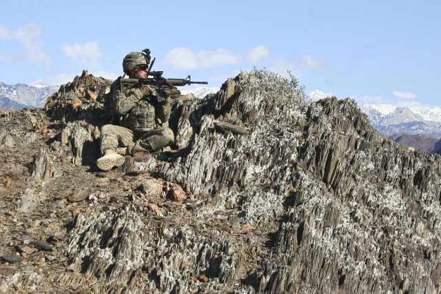 Sgt. Nick Andrews, an infantry squad leader with Company C, 1st Battalion, 133rd Infantry Regiment, from Marshalltown, Iowa, looks into the valley from a mountaintop outside the village of Nengaresh, Afghanistan, Jan. 21. Soldiers from Co. C, joined Afghan National Army Soldiers from Weapons Company, 1st Battalion, 201st Infantry Corp, on the patrol.