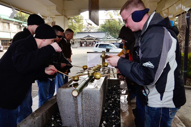 Members of the 64th Rear Operations Center, Wisconsin National Guard, share Japanese traditional customs as they purify their hands and body before entering the Kumamoto Castle Jan. 24 as a part of a cultural exchange during Yama Sakura 59, which began Jan. 22 in Kumamoto, Japan.