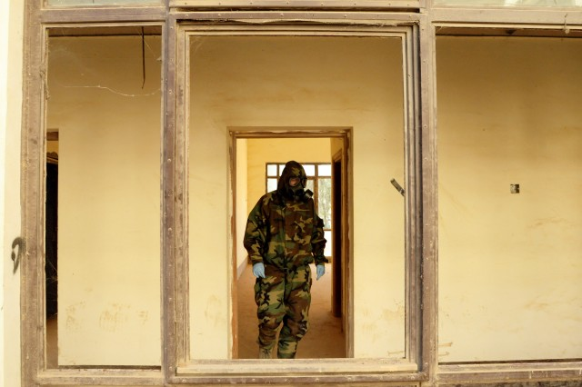 BAGHDAD - An Iraqi Army Chemical Defense Regiment Soldier searches a facility that a capabilities exercise scenario dictates is suspected to house munitions at Camp Taji in early December.