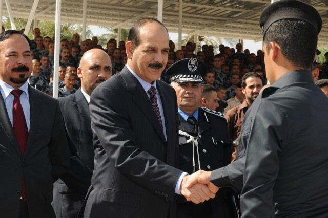 BAGHDAD - Iraq's Minister of Interior Jawad Al-Bolani (center) congratulates a graduate from the first class consisting of 300 Police commissioners to graduate from the Police Commissioner Institute, a vocational high school commissioned by Iraq's Ministry of Interior, during a graduation ceremony held at the Baghdad Police College Parade Field here in late October.