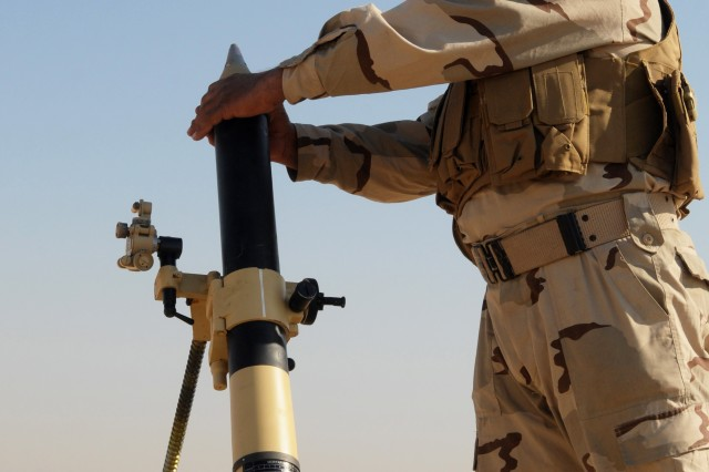 BAGHDAD - An Iraqi Army infantry Soldier prepares to fire an 81mm mortar during a live-fire exercise at the Besmaya Combat Training Center in late November. Infantry Soldiers from the Iraqi Army's 1st, 11th and 17th divisions fired high-explosive anti-tank and white phosphorous smoke rounds as part of the culminating exercise to a 21-day Basic 81mm Mortar Course.