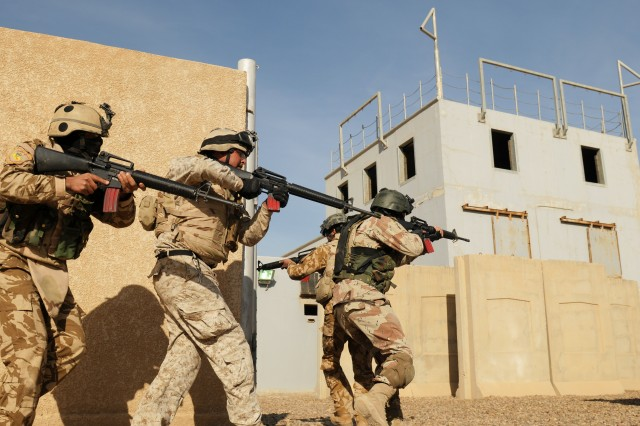 BAGHDAD - Iraqi Army Soldiers with 2nd Company, Commando Battalion, 11th Iraqi Army Division, based out of Joint Security Station Old Ministry of Defense in Baghdad, prepare to enter and clear a building during an urban operations live-fire exercise at Camp Taji in late December. United States Forces-Iraq Soldiers from the U.S. Army's Co. B, 1st Bn., 18th Inf. Regt. advised the Iraqi commandos on room clearing instruction, urban tactics and fire team exercises.